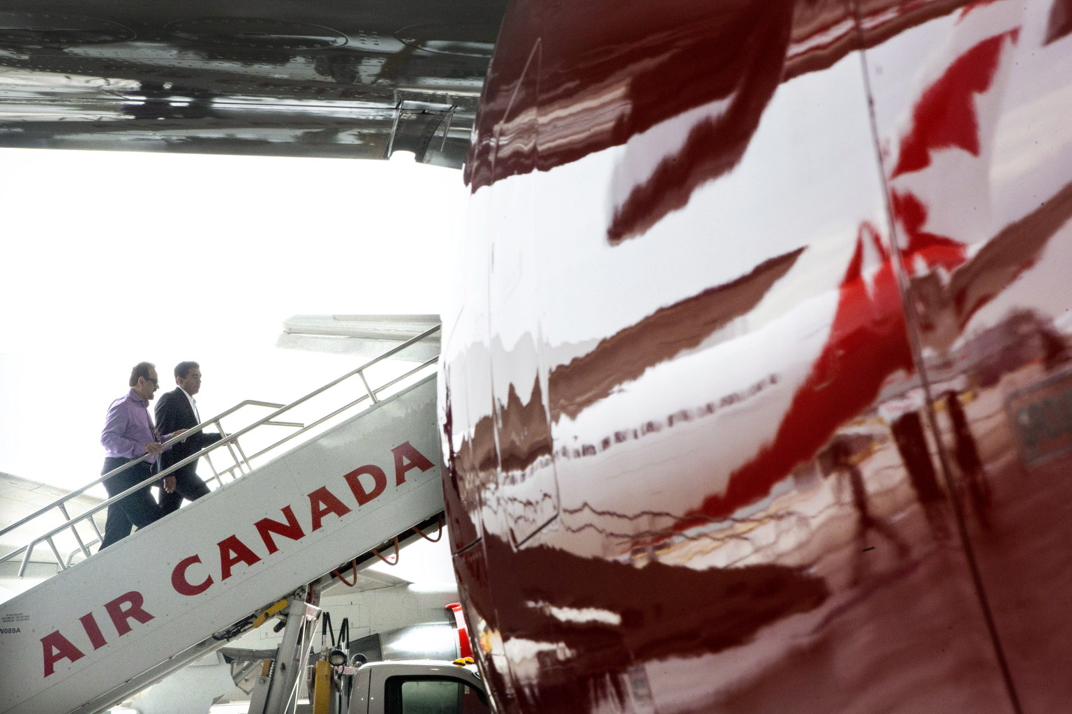 "Guests climb aboard a plane in an Air Canada hanger at Toronto's Pearson Airport on Tuesday June 25, 2013, as the airline launches it's new ""leisure carrier"" Air Canada Rouge. THE CANADIAN PRESS/Chris Young"